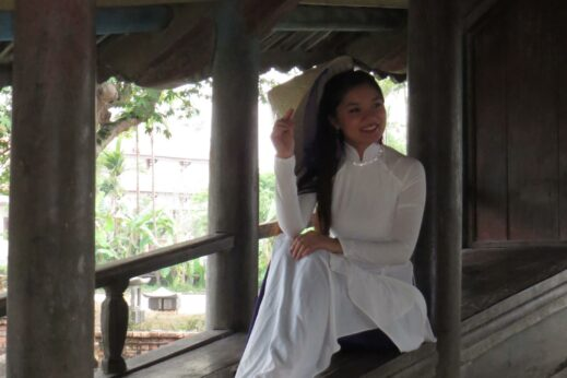 A girl wearing a traditional Ao Dai outfit on a bridge in the Hue countryside