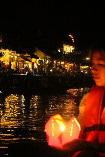 Setting lanterns adrift as we float along the Thu Bon River