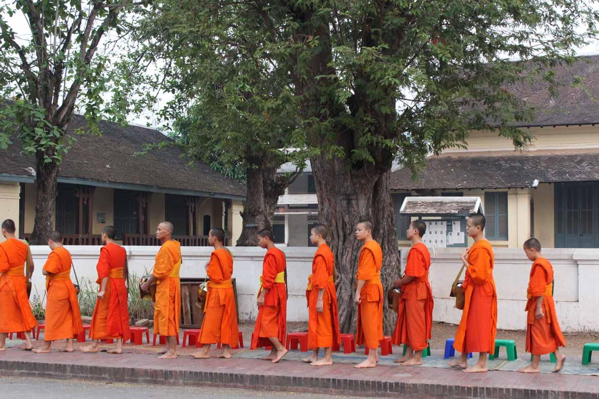 Monks file past during the morning alms