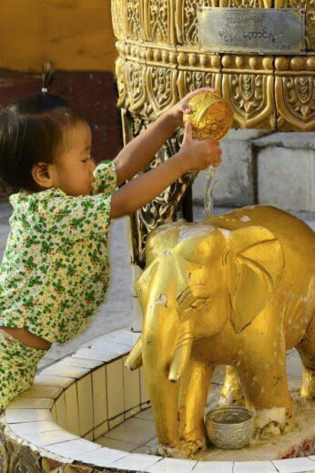 Burmese girl washes elephant statue