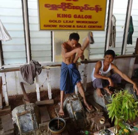 Workers hammering out gold leaf in Mandalay