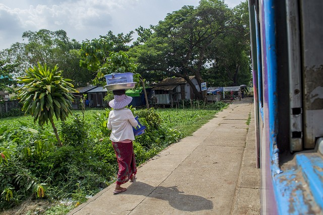 A lady carrying washing on her head outside Yangon's circle train, Burma (Myanmar)