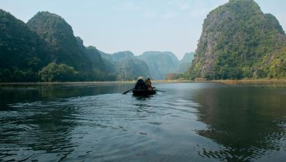 A longboat paddling through karst landscape in Vietnam