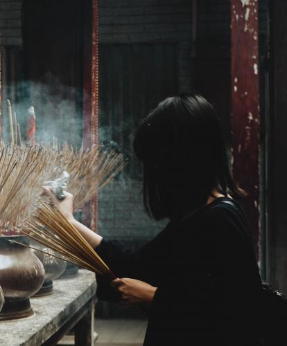 A woman lights incense at a shrine