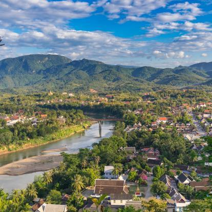 Aerial view of beautiful Luang Prabang city surrounded by jungle and sprawling alongside Nam Khan River