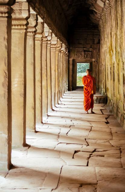 Monk walking under temple arches