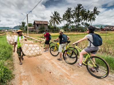 Biking along dusty roads past local villagers