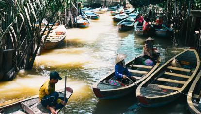 Boats on a narrow stretch of river in the Mekong Delta