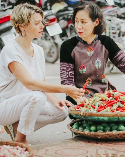 A local chef takes shows off produce at a market in Vietnam